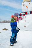 Boy makes a snowman Stock Photos
