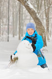 Boy makes a snowman Stock Photo