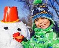 Boy makes a snowman Stock Photo