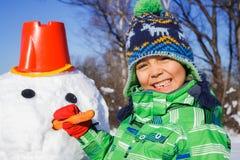 Boy makes a snowman Royalty Free Stock Image