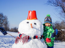 Boy makes a snowman Stock Images