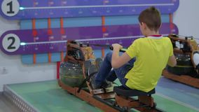 Boy makes sport exercises on training apparatus in scientific museum. The boy pulls their legs and burns calories. Special plate shows child how long he is stock video footage