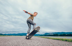 Boy makes a trick with skateboard Royalty Free Stock Image