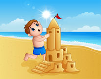 Boy making a big sand castle at the beach Royalty Free Stock Images