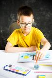 Boy making a colorful drawing at home. Young boy making a colorful drawing at home royalty free stock photo
