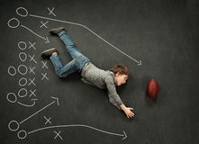 Boy making a diving catch for football. With football play around him Stock Image