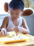 Boy making dumplings Stock Photos