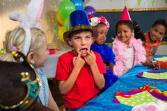 Boy making face while sitting with friends Royalty Free Stock Photography