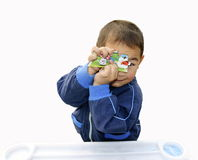 Boy making faces. A candid picture of a little chinese boy making faces while playing jigsaw games Royalty Free Stock Image