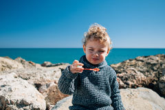 Boy making faces blowing soap bubbles. Portrait of blonde kid with windy hair blowing soap bubbles against of seascape Royalty Free Stock Images