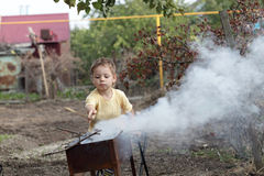 Boy making fire in a grill Royalty Free Stock Images