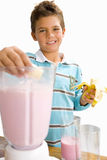 Boy making fruit smoothie, smiling, portrait, cut out Stock Photography