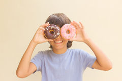Boy making fun with donuts. Teen boy making fun with multicolored donuts Stock Photos