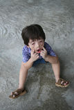 Boy making funny face. Boy sitting on the floor making funny face royalty free stock photo