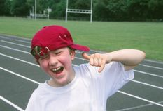 Boy Making Hang Loose Sign. Nine year old boy making hand loose sign on a sports track Royalty Free Stock Photo