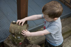 Boy making house out of wood logs. A close up of a young boy making a house out of wood logs royalty free stock photo