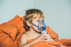 Boy making inhalation with a nebulizer at home Stock Photos
