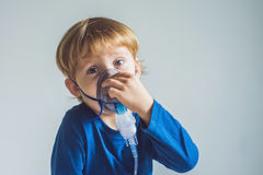 Boy making inhalation with a nebulizer at home stock image