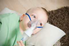 Boy making inhalation with nebulizer at home Stock Image