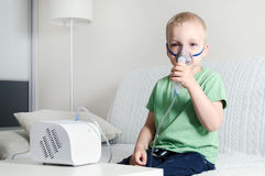 Boy making inhalation with nebulizer at home Stock Photo
