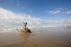 Boy making an island in the sea stock photography