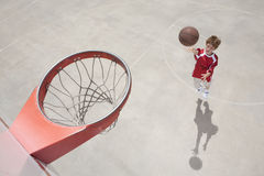 Boy making jump shot Royalty Free Stock Photo