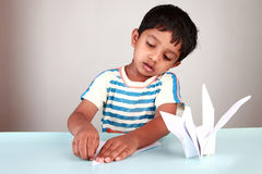 Boy making paper bird Stock Photo