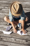Boy making a paper boats on the wooden pier Royalty Free Stock Photo