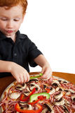 Boy making pizza. Young boy preparing homemade pizza closeup isolated on white Royalty Free Stock Image