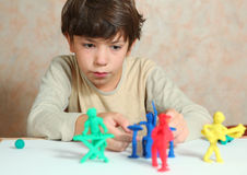 Boy  making rock group musician from modeling clay. Boy  making rock group musician  from modeling clay Royalty Free Stock Images