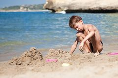 Boy making sand castle on beach Royalty Free Stock Photos