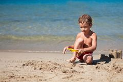 Boy making sand castle on beach Royalty Free Stock Photo