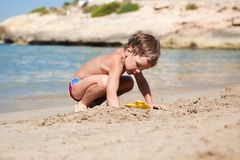 Boy making sand castle on beach Stock Image