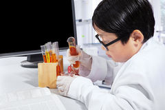 Boy is making science experiments. Portrait of a little boy is making science experiments while wearing glasses and coat in the laboratory Stock Photo