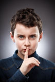 Boy making silence sign Stock Photos