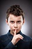 Boy making silence sign Stock Photos