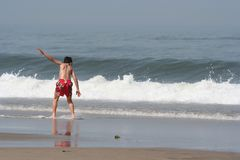 Boy making skimming. At the coastline Stock Image