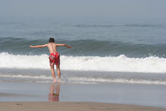 Boy making skimming. At the coastline Stock Images