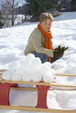 Boy (7-9) making snow ball pile on sled in snow field, smiling, portrait Royalty Free Stock Image