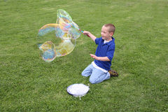 Boy making soap bubbles Stock Images
