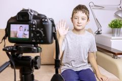 A boy, male child video blogger recording vlog or podcast, streaming online. Blurred camera on tripod in front stock photos