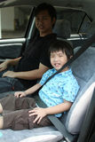 Boy & man buckle up seat-belt. Boy and man buckle up seat-belt sitting in the car Stock Photography