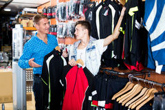 Boy with man choosing sport jackets for cycling Royalty Free Stock Image