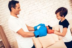 Father and Son in Boxing Gloves Greet Each Other. Boy with Man. Father and Son Boxer. Sport at Home. Warm Up in Quarter. Greet Each Other. Boxing Gloves. Doing stock image