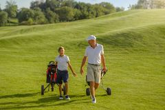 Boy and man golfers walking on golf course with carts stock photography