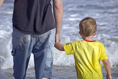 Boy and Man holding hands in ocean waves Royalty Free Stock Photo