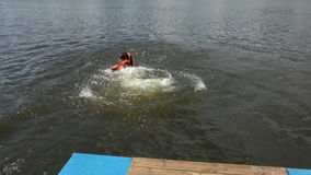 A boy and a man jumping into the water stock video footage
