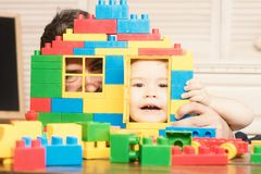 Boy and man play together. Father and son looking through door and window of toy construction. Family games concept. Kid. Boy and men play together. Father and royalty free stock images