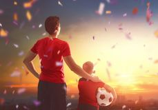 Boy with man playing football stock images