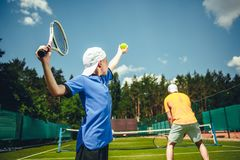 Boy and man playing tennis stock images